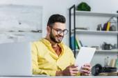 Usmíval se vousatý podnikatel v brýlích při pohledu na obrazovku tabletu v kanceláři