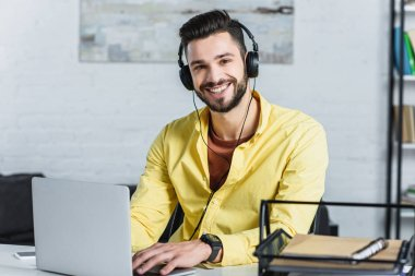 Cheerful bearded businessman with headphones looking at camera at office