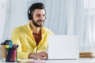 Smiling bearded businessman in headphones looking away at workplace