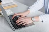 Fotografia Ritagliate la vista della donna digitando sulla tastiera del computer portatile