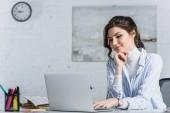 Atraktivní podnikatelka, při pohledu na obrazovku notebooku v práci