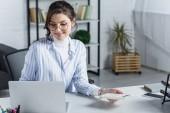 atraktivní žena v brýlích, drží Kalkulačka u notebooku v moderní kanceláři