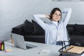Photo thoughtful woman in glasses sitting near laptop in modern office