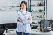 Photo attractive woman standing with crossed arms in modern office