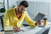 cheerful man writing in notebook and holding book in hand in modern office