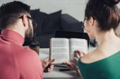 selective focus of book in hands of colleagues in modern office