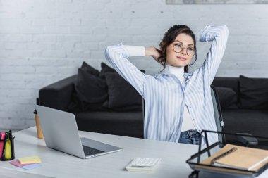 thoughtful woman in glasses sitting near laptop in modern office