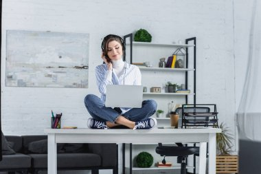happy woman in headphones sitting on table with laptop