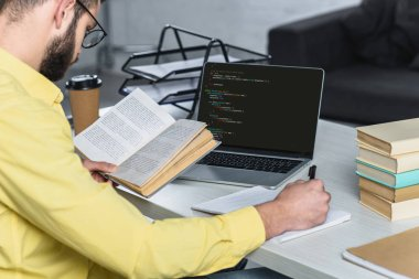 bearded man studying with book near laptop with computer coding on screen in modern office