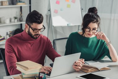 attractive woman in glasses studying with book near coworker using laptop