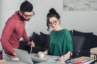 attractive woman in glasses writing in notebook near coworker