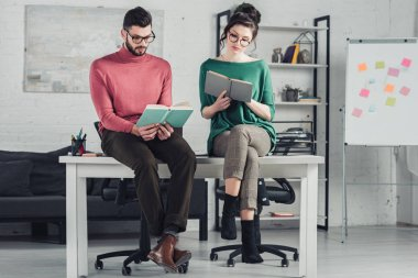 coworkers studying with books while sitting on table in modern office