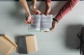 top view of coworkers holding book in hands