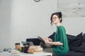 töprengő nő, tanulmányozza a könyvet, és ül a kanapén