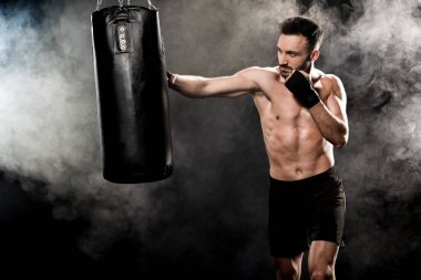 Shortless athletic boxer exercising with punching bag on black with smoke stock vector