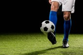 oříznutý pohled člověka hrát s míčem na trávě izolované na černém pozadí