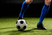 verkürzten Blick auf Sportler spielen mit Ball auf dem grünen Rasen, isoliert auf schwarz