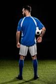svalnatý sportovec v uniformě, držení míče, samostatný na černém
