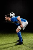 Fotografie sportsman in uniform training with ball on grass isolated on black