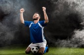 Fotografie handsome football player celebrating victory while sitting on grass on black with smoke