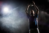 Fotografie silhouette of cheerful football player holding ball above head on black with smoke