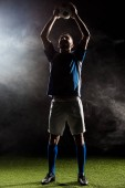 silhouette of football player holding ball above head on black with smoke