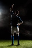 Photo silhouette of football player holding hand above head on black with smoke