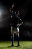 Fotografia Siluetta del giocatore di gioco del calcio che tiene la mano sopra la testa sul nero con fumo