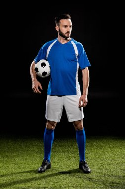 handsome football player standing with ball on green grass isolated on black