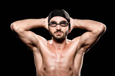 Handsome swimmer posing in swimming cap and goggles isolated on black stock vector