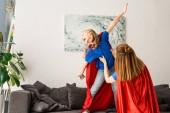Dítě a matka v červených pláštích hraní a usmívá se doma