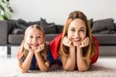 Dcera a matka při pohledu kamery na podlaze