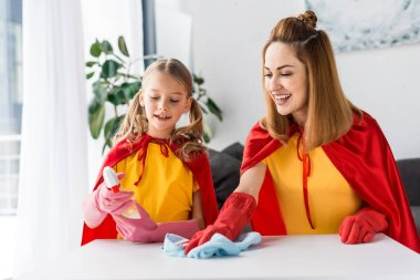 Mother and daughter in red capes and rubber gloves dusting at home stock vector