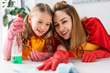 mother and daughter in red capes and rubber gloves cleaning at home