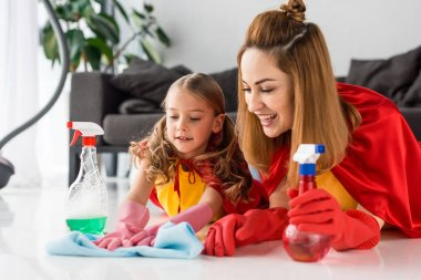 mother and kid in red capes and rubber gloves with sprays washing floor