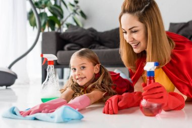 mother and cute kid in red capes and rubber gloves washing floor at home