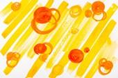Fotografia Vista superiore del cerchi arancioni e pennellate di gialle su fondo bianco