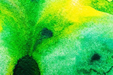 top view of yellow and green watercolor spills with copy space
