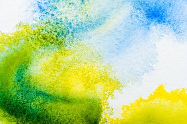 Top view of blue, yellow and green watercolor spills on white paper stock vector