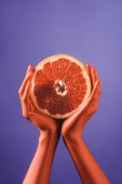 partial view of woman holding cut grapefruit in coral colored hands on blue background, color of 2019 concept