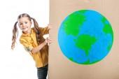 Fotografie roztomilé dítě drží lepenky štítek se symbolem zeměkoule izolované na bílém, koncept den země