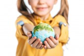 Photo selective focus of cute child holding globe model in stretched hands isolated on white, earth day concept