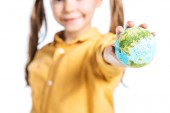 Photo selective focus of smiling kid with globe model in stretched hand isolated on white, earth day concept