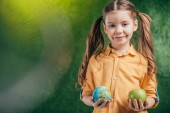 child holding globe model and apple on blurred background on blurred background, earth day concept