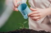 Selektivní fokus dítě drží modré hračky konev a mladých zelených rostlin na rozostřeného pozadí, koncept den země