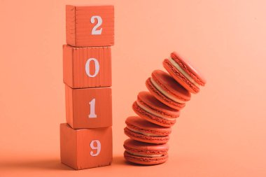 Stack of wooden cubes with 2019 numbers and macarons on coral background, color of 2019 concept stock vector