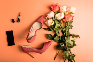 coral roses bouquet, shoes, coral lipstick and smartphone on coral background, color of the year 2019 concept