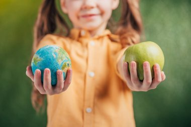 selective focus of child holding globe model and apple on blurred background, earth day concept