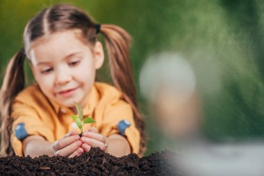 Selective focus of cute kid planting young plant on blurred background, earth day concept stock vector