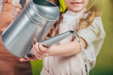 selective focus of woman and kid with watering can on blurred background, earth day concept